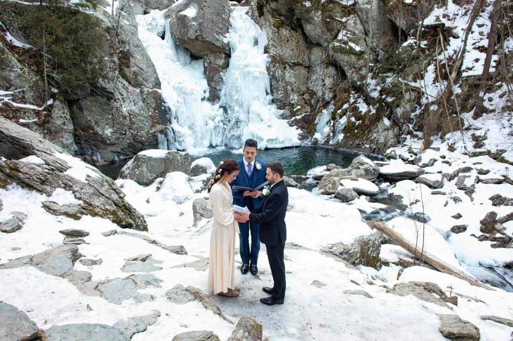 Frozen Bash Bish Falls behind elopement couple